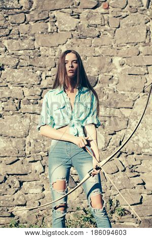 Cute girl archer or pretty woman with long hair and blue jean clothes holding bow and arrow on sunny summer day on stone wall. Ambition direction target
