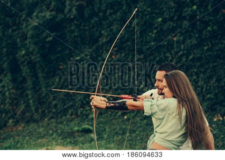man and pretty woman or cute girl with long hair archers or hunters shooting with bow and arrow on summer day on green natural background. Couple in love. Concentrate and aiming