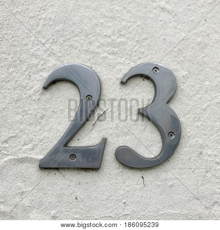 Number 23 silver metal house number address sign screwed into painted white stone wall textured background