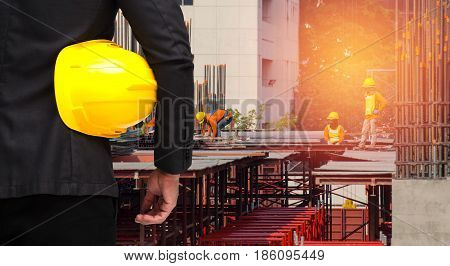 back view of smart construction manager in suite with yellow safety helmet on construction site worker working at construction site background industrial concept sunlight effect
