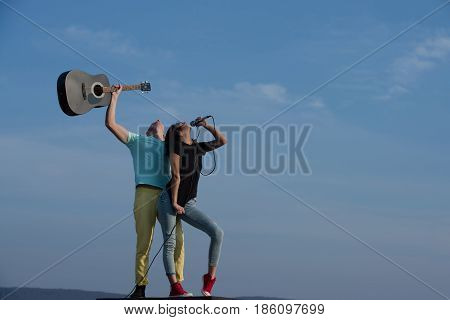 Romantic Couple Of Musicians Performing On Table On Blue Sky