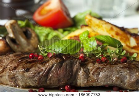 closeup of a beef steak with peppercorns