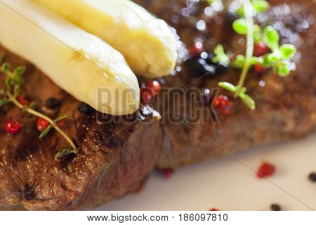 closeup of white asparagus on a grilled steak