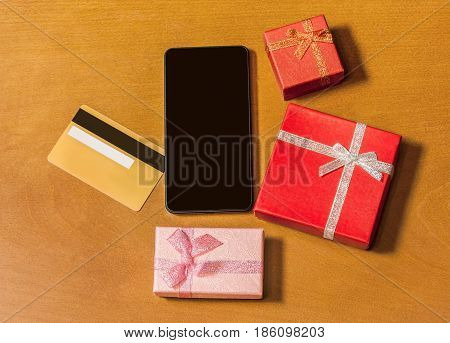 Smartphone and gift boxes on wood background