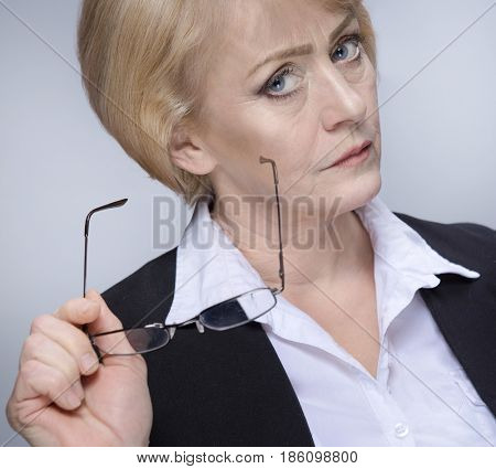 Beautiful Matured Woman serious angry upset gloomy caucasian in glasses blond studio shot looking at camera. Grey background. Businesswoman in suit. Retired