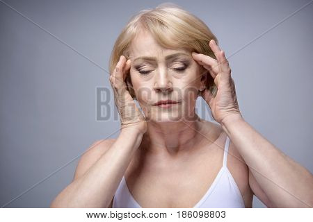 old mature woman portrait face closeup eyes closed hands headache studio shot