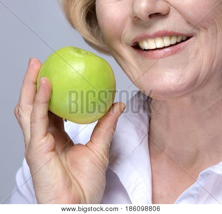 Beautiful Matured Woman cheerful caucasian with green apply toothy smile studio shot. Grey background.Copy space. Dental. Stomatology. Perfect white teeth. Healthy eating concept. Raw vegetarian fruit