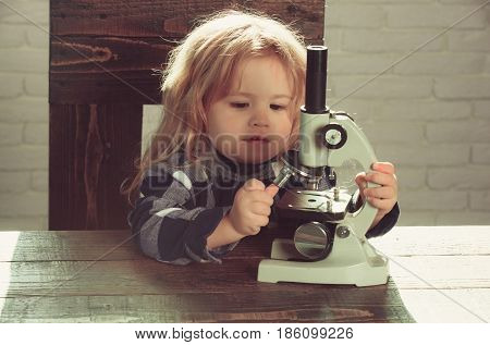 boy student studying at his workplace with microscope educational concept