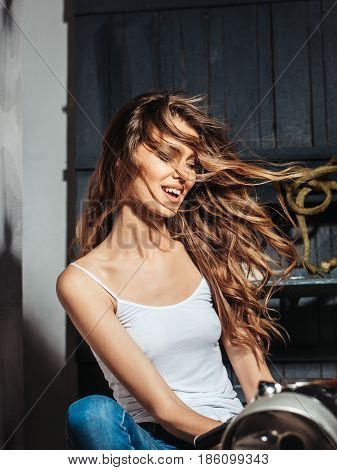 Happy Sexy Biker With Curly, Long, Blond Hair On Motorcycle