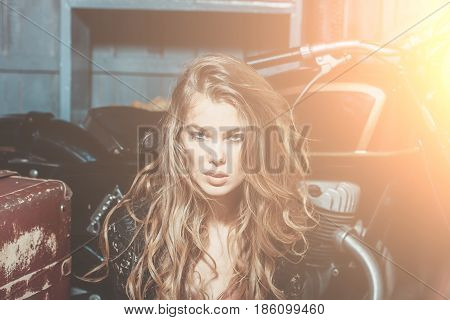 beauty. fashion model or beautiful woman and girl with pretty face makeup and stylish blond curly long hair sitting at metallized motorcycle on garage background. Motorcycling hobby and lifestyle