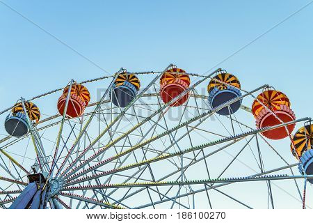 Classic Ferris wheel on blue sky background. Entertainment Park attraction with retro booths.