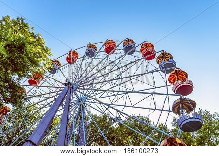 Classic Ferris wheel. Entertainment Park attraction with retro booths.