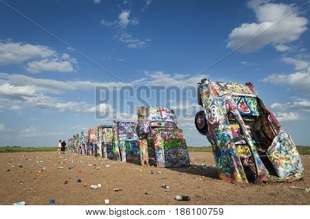 Amarillo Texas - July 8 2014: Row of brightly painted Cadillacs in the Cadillac Ranch in Amarillo Texas USA.