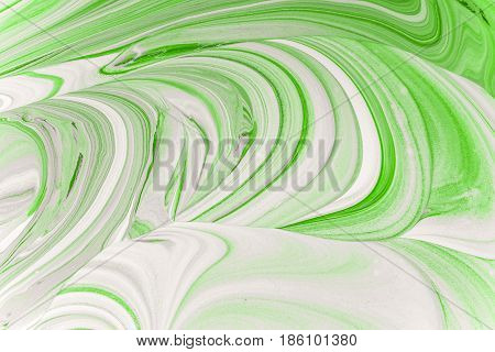 Mixing green color with a bright white interior acrylic paint. Mix liquid paint. Abstract texture.