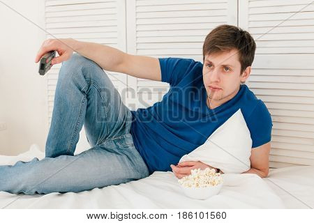 Man Watching Tv Sitting On The Bed Eating Popcorn