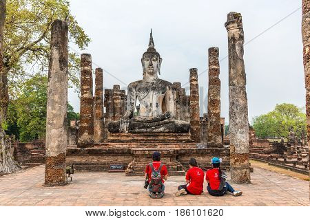 SUKHOTHAI THAILAND - APRIL 1 2016: Three people with red T-shirts worshipping Buddha Image in Sukhothai historical park Sukhothai.