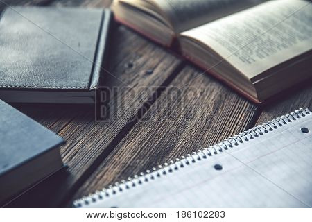 Business concept, ideas, books and exercise book on a wooden background with pencils a