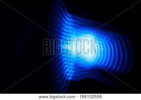 Sound waves in the visible blue color in the dark. Soft focus