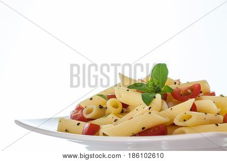 Penne rigate with cherry tomatoes and black pepper on white background