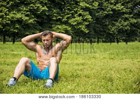Portrait of topless sportsman with tattooes doing exercise on abdominal in summer park