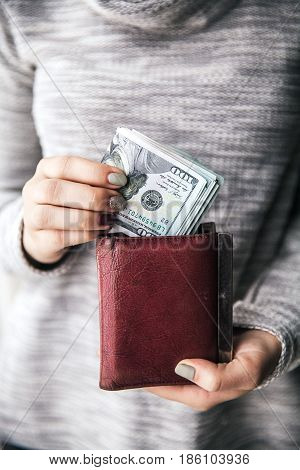 In the women's hands is the brown leather wallet with a wad of hundred dollars. Business offer. Beautiful manicure a
