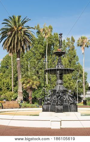 Auckland New Zealand - March 5 2017: Black metal 19th century Victorian Fountain in center of Albert Park. Green vegetation tall palm tree and people in back under blue sky.
