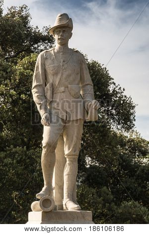 Auckland New Zealand - March 5 2017: Closeup of soldier at South African War Artillery Memorial in Albert Park. White stone on pedestal. Green trees in back. Mostly white sky.
