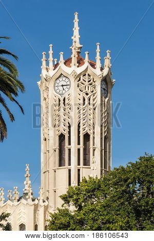 Auckland New Zealand - March 5 2017: Closeup of White clock tower top of Auckland University under blue sky. Some green tree leaves.