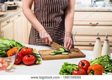 Young woman cooking in the kitchen at home. Healthy food. Diet. Dieting concept. Healthy lifestyle. Cooking at home. Prepare food. A woman cuts a cucumber and vegetables with a knife.