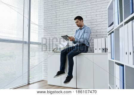 Serious businessman sitting on dresser with tablet computer