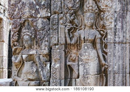 Beautiful Cambodian women dancing Apsaras. Old Khmer art carvings on the wall of Prasat Bayon the central temple of Angkor Thom Complex, Siem Reap, Cambodia.