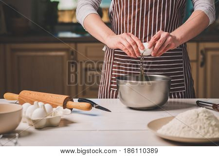 Young woman breaking egg over bowl with dough, close-up. A woman in a striped apron is cooking in the kitchen