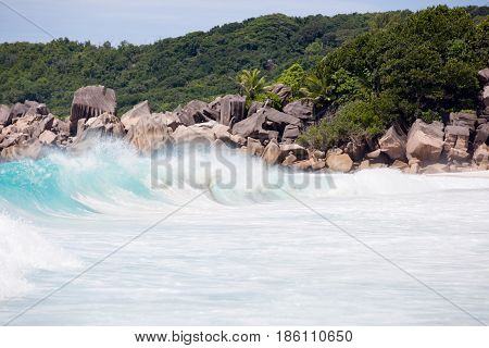 Tropical beach, wild waves, turquise water of the Indian ocean next to typical granite rocks of Seychelles