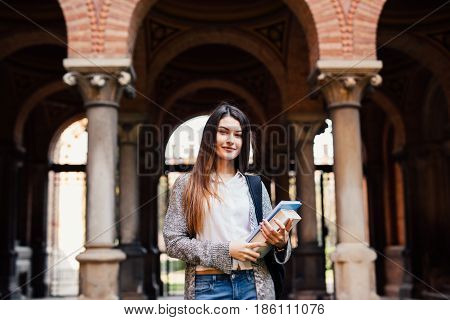 Smiling Female Student With Books Outdoor Near University