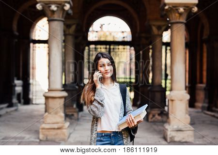 Gorgeous Happy Student Holding Notebooks Speak Phone On Campus At College