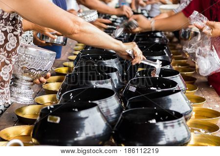 people put rice into the monk's bowl on holy day.