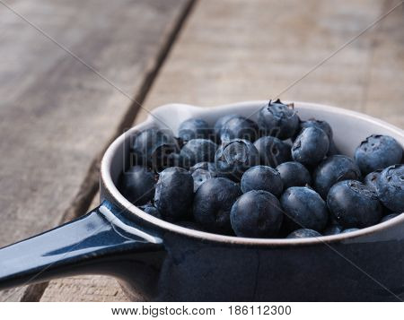 Fresh organic blueberries in a rustic blue bowl on old wooden plank