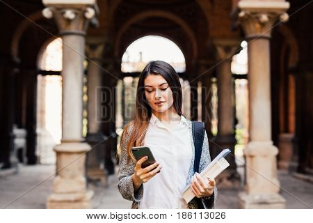 Gorgeous Happy Student Holding Notebooks Texting On Campus At College