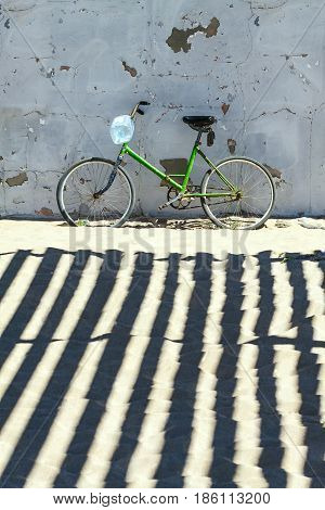 classic bike green color is the gray wall. Sandy beach and shade on the ground.
