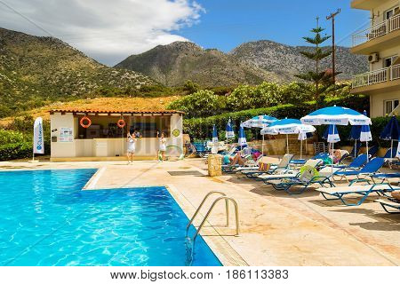 Bali Greece - May 2 2016: Animation at Resort hotel Atali Village 4 star. Cute girls in white beach suit girls dancing in front of swimming pool with clean blue water for tourists. Crete island