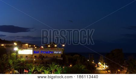 Bali Greece - may 2 2016: Exterior of resort Bali Paradise Hotel building surrounded by tropical gardens on paved street with parked cars leading to sea beach. Village Bali Rethymno Crete Greece