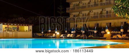 Bali Greece - May 2 2016: Empty swimming pool with lighting without tourists at night in hotel. Relax by pool with clear blue water in Resort hotel Atali Village 4 star. Rethymno Crete Greece