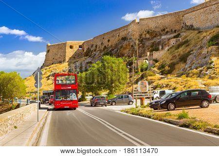 Rethymno Greece - May 3 2016: Red open double-Decker sightseeing bus traveling on highway along promenade Emmanouil Kefalogianni. Venetian fortress Fortezza Castle hill Paleokastro in Crete resort