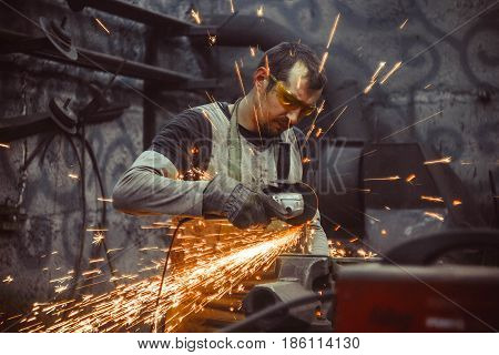 worker sawing metal with a saw sparks fly