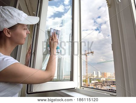 Woman washing the window. Female worker of cleaning company. Construction site outside the window in the background