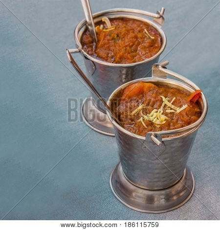 Prawn balti, an Indian dish, served in the typical dishware, square photo