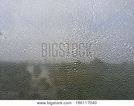 Rain drops on the window see blurry thru the park and the dark cloudy sky behind. selective focus lens blur