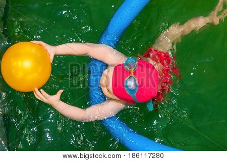 Top view of a toddler girl learning to swim with a pool noodle in a seawater swimming pool