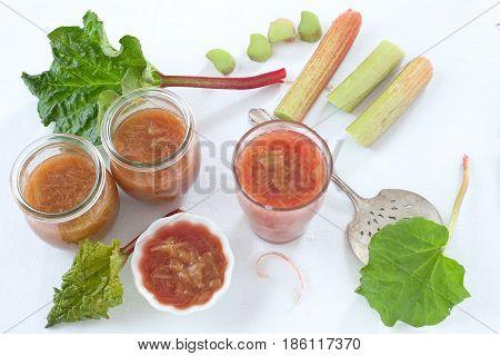 Homemade rhubarb sauce in a glass jar and fresh rhubarb.