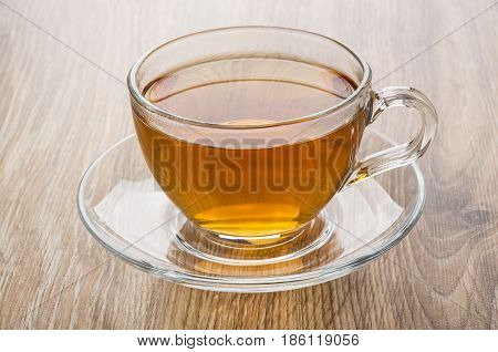 Tea In Transparent Glass Cup With Saucer On Table
